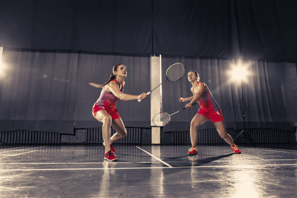 young women playing badminton at gym - badminton stock pictures, royalty-free photos & images