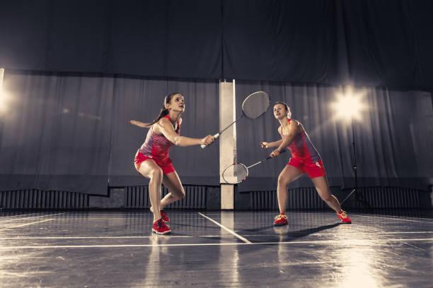 mujeres jóvenes jugando badminton en el gimnasio - bádminton deporte fotografías e imágenes de stock