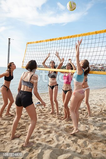 Young women in teams by the volleyball net on the beach, ball in the air for spiking