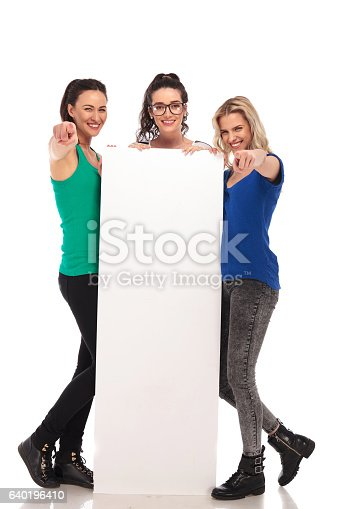 istock 3 young women pointing fingers while holding big blank board 640196410