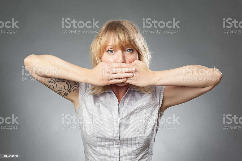 Young women portrait on grey background, covering her mouth stock photo