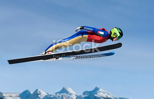 Side view of young  female ski jumper in mid-air