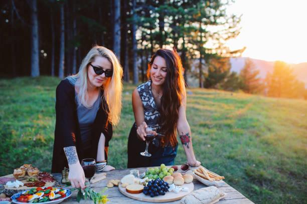 junge frauen, die vorbereitung von essen und wein für picknick im grünen - käse wurst salat stock-fotos und bilder