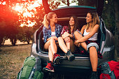 Three young woman hiking together in nature. Taking hiking equipment from the car and taking hiking shoes on, preparing for camping. Sitting in car trunk and talking. They are best friends from elementary school. Real people.