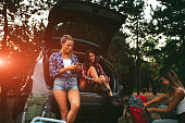 Three young woman hiking together in nature. Taking hiking equipment from the car and taking hiking shoes on, preparing for camping. Sitting in car trunk. They are best friends from elementary school. Real people. Young woman left side holding smart phone and typing on it.