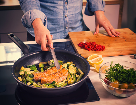 Young women preparing salmon with asparagus and zucchini at home