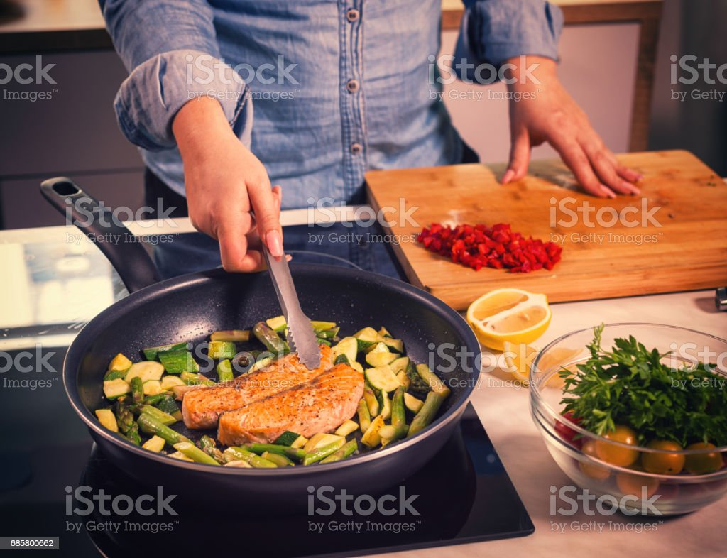Young Women Preparing Salmon at Home stock photo