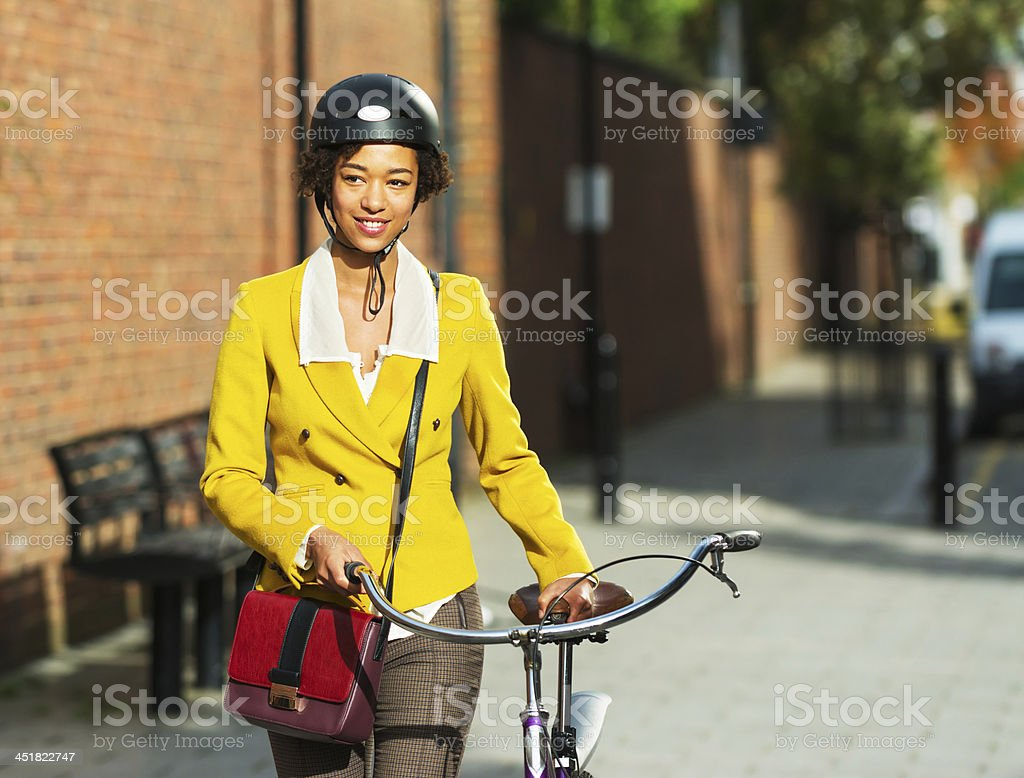 Young women pushing her bike in the city stock photo