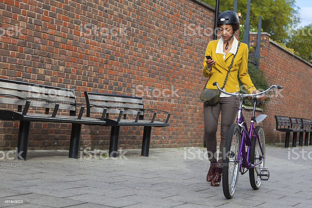 Young women pushing her bike in the city royalty-free stock photo