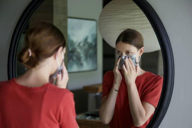 jonge vrouwen die op wegwerp chirurgisch masker zetten alvorens van huis uit te gaan. corona virus uitbraak of luchtvervuiling halth zorg concept. - mirror mask stockfoto's en -beelden