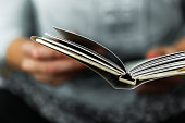 istock Young Women Reading A Small Book 1127066336