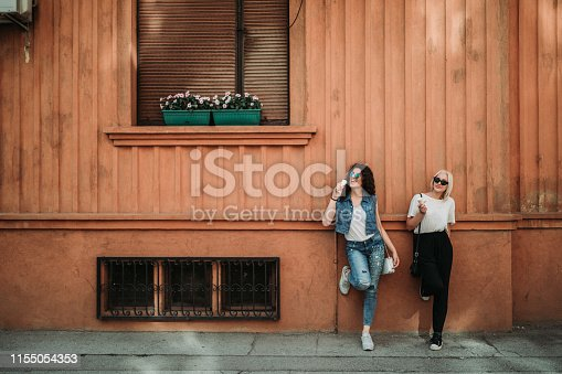 1092709104 istock photo Young women relaxing in the city street and eating ice cream 1155054353