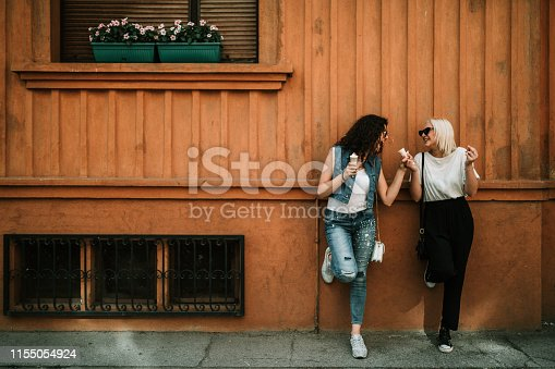 1092709104 istock photo Young women relaxing in the city street and eating ice cream 1155054924