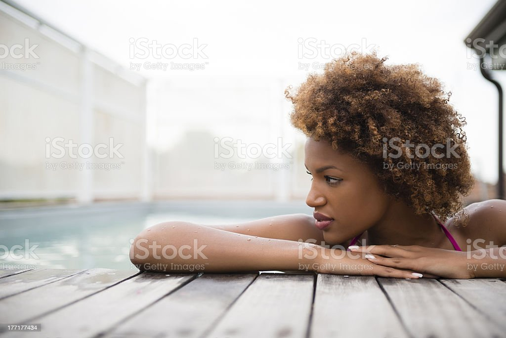 A young women relaxing inside of a pool royalty-free stock photo