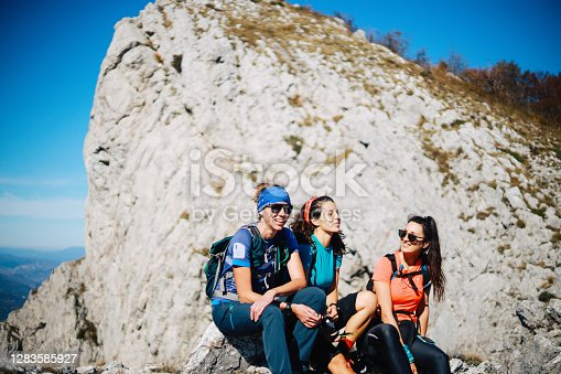 Three young women resting after hiking in the beautiful outdoors. They are having a relaxed time together, enjoying the autumn nature, wearing sports clothes. After the adventure, they are sitting on the mountain on a nice sunny day.