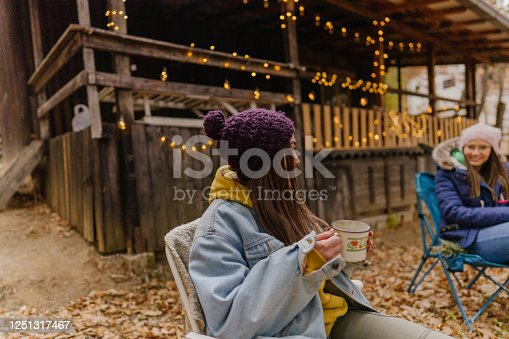 Photo of young women enjoying a cup of hot chocolate outside the log cabin, on a cool autumn day.