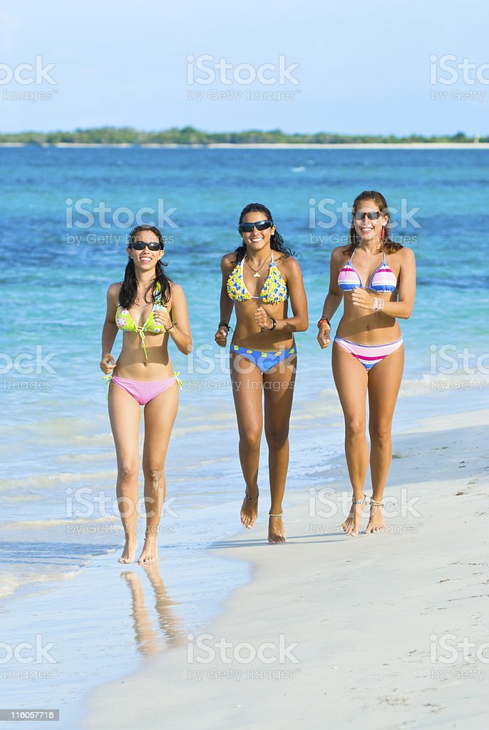 Young Women running in a beach stock photo