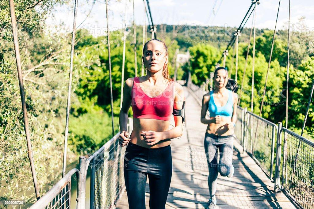 Young women running on rope bridge stock photo