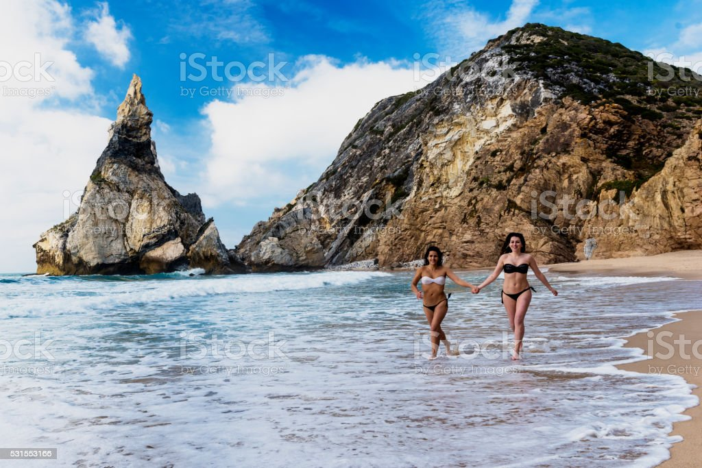 Young women running on the sandy beach, beautiful landscape stock photo
