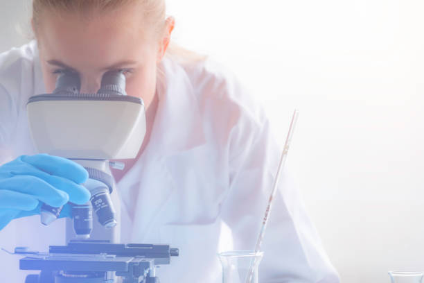 young women scientist or doctor looking through a microscope in a laboratory. young scientist doing some research,science and medical research and development concept - microscope stock photos and pictures
