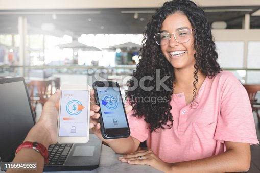 Young women sending money through digital wallet, using wireless technology. Selective focus on smartphone screen. Personal perspective