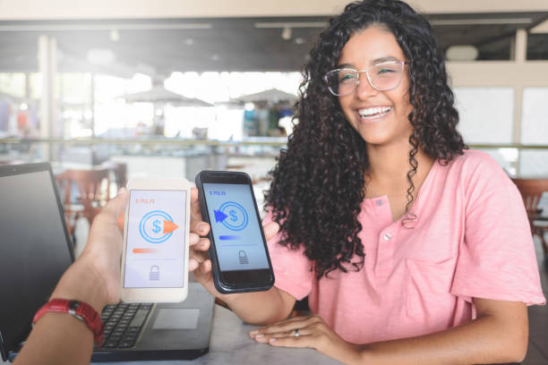 Young women sending money through digital wallet, using wireless technology stock photo