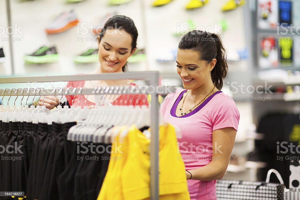 young women shopping for clothes in sports shop stock photo