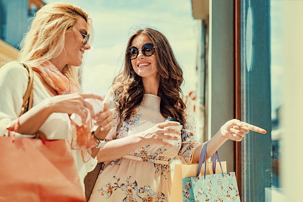 young women shopping in the city - kleider günstig kaufen stock-fotos und bilder