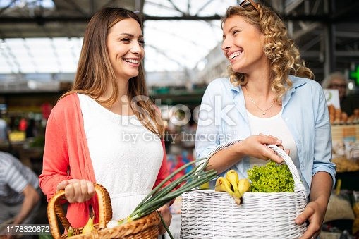 Young happy women shopping on the market healthy vegetables and fruits