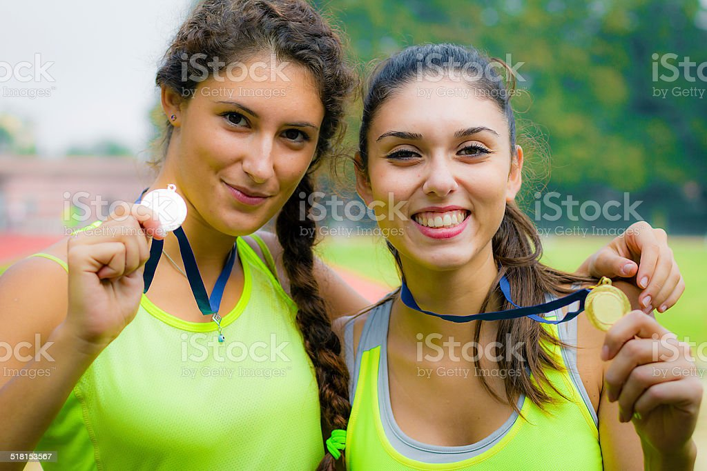 Young women showing gold medals stock photo