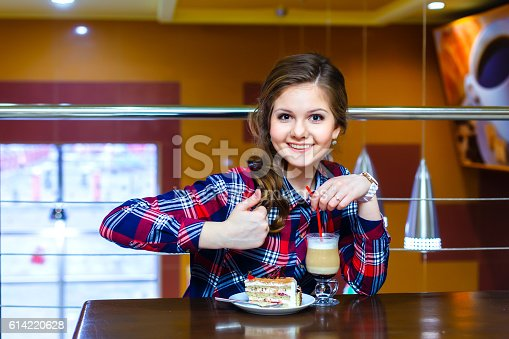 young beautiful women shows thumbs up to cup of mokachino and cake in cafe