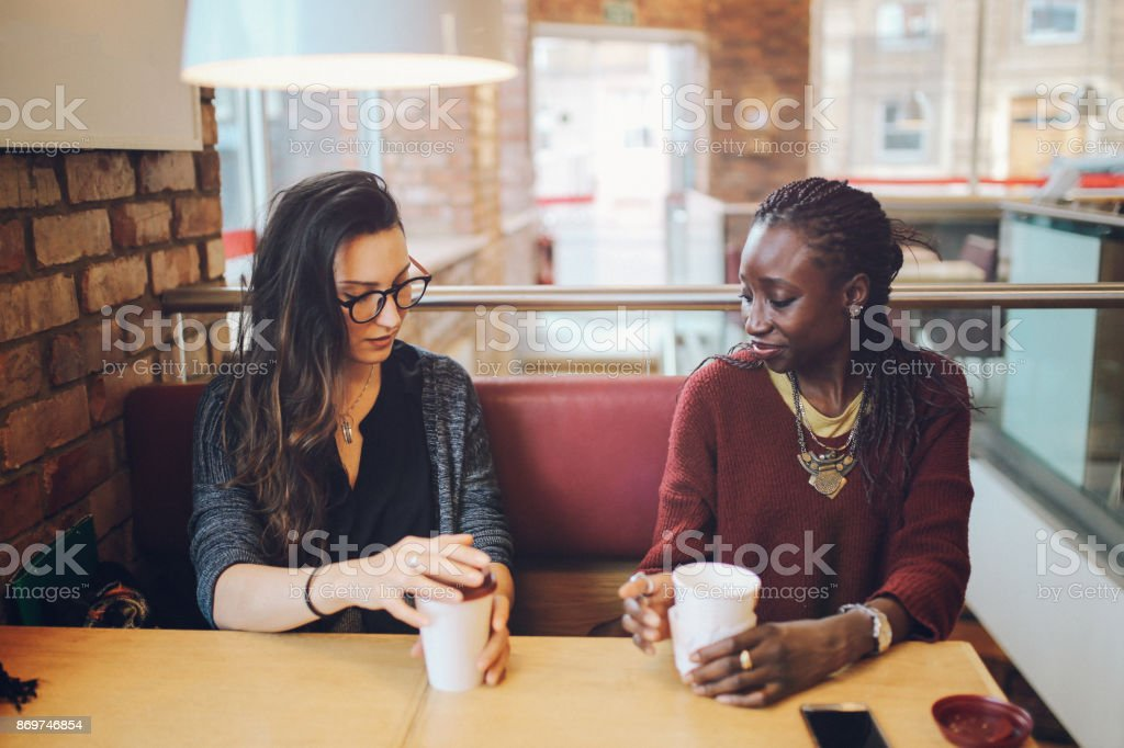 Young women sitting and talking at the coffee break stock photo