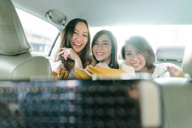 junge frauen sitzen in einem taxi mit einkaufstüten - happy weekend bilder stock-fotos und bilder