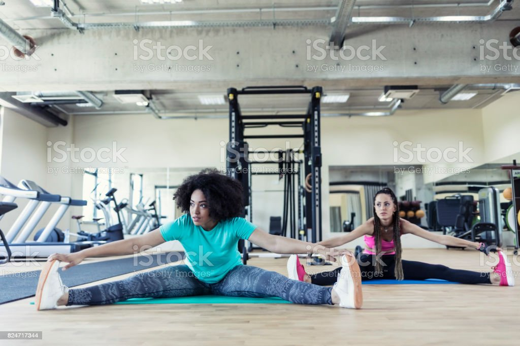 Young women sitting on floor and stretching in gym stock photo
