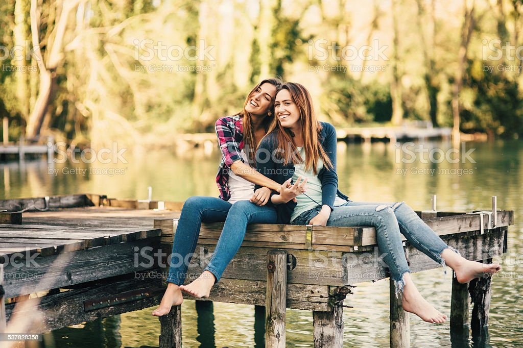 Young women sitting on the pier stock photo