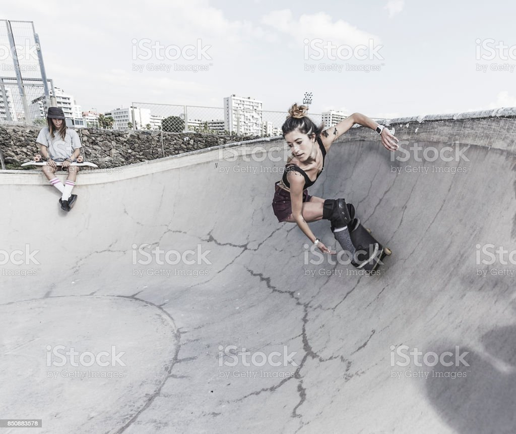 Young women skateboarding in skatepark stock photo
