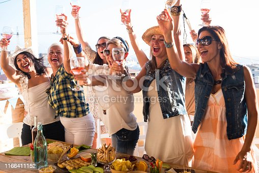 1016084100istockphoto Young women smiling and laughing while celebrate a birthday and an upcoming wedding. Seven people on the terrace field enjoying aperitif and food. Wooden table on background 1166411152