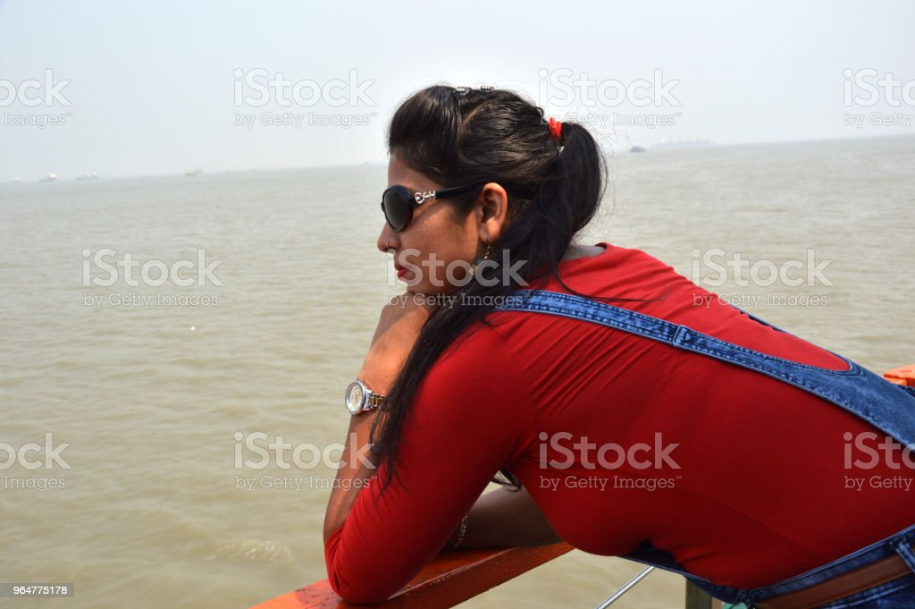 A young women standing in ship the middle of sea water . royalty-free stock photo