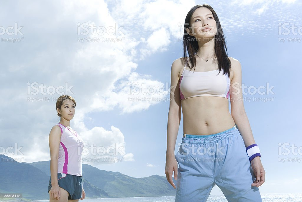 Young women standing on beach, looking away royalty-free stock photo