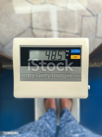 Close up young women legs, standing on weight scale to measure her weight.