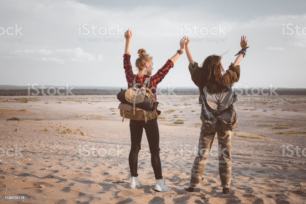Young women standing with arms raised in desert Full length of young women standing with arms raised. Rear view of female hikers are holding hands on sand. They are looking at desert landscape. 20-24 Years Stock Photo