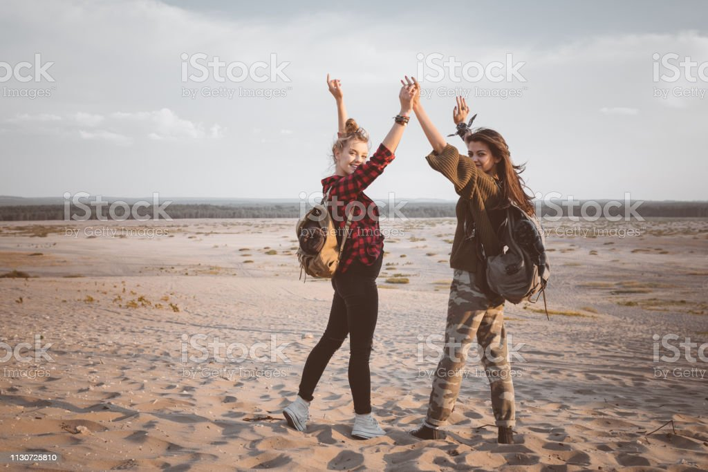 Young women standing with arms raised in desert Smiling female hikers looking over shoulder while holding hands. Full length portrait of young women are standing with arms raised. They are standing with backpacks at desert. 20-24 Years Stock Photo