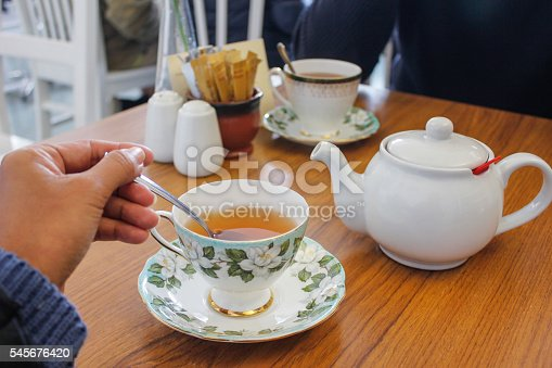 Young women stirring a cup of tea