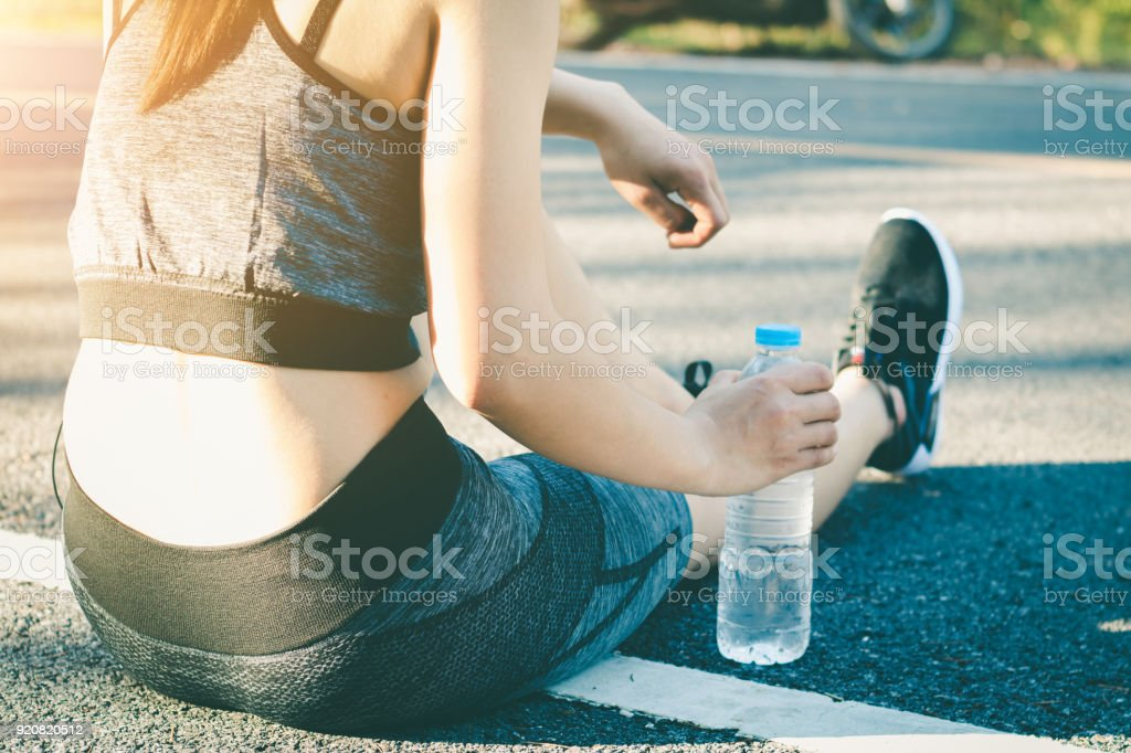 Young women stops drink water resting after running. stock photo