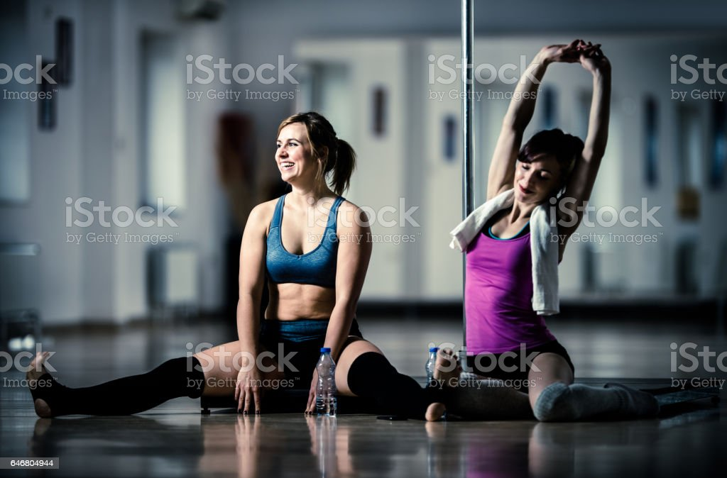Young women stretching after pole dancing in a dance studio. stock photo