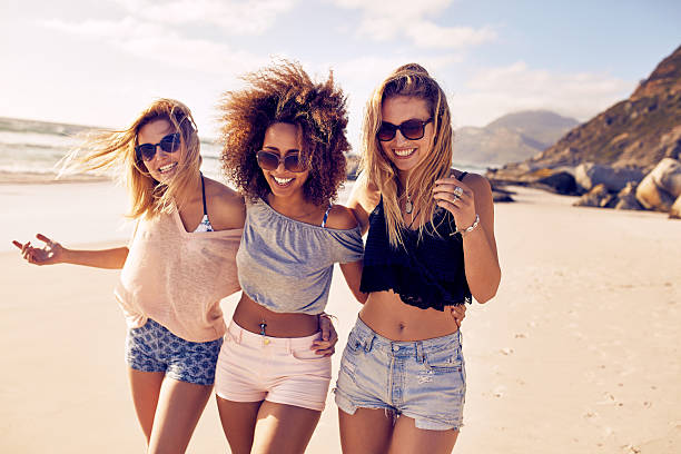 young women strolling along a beach - beach fashion stock photos and pictures