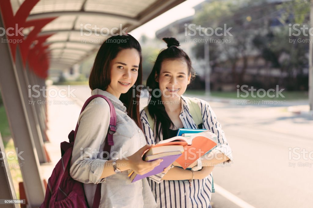 Young women students together study reading book in university and knowledge at outside or park campus relaxing smile in summer season stock photo