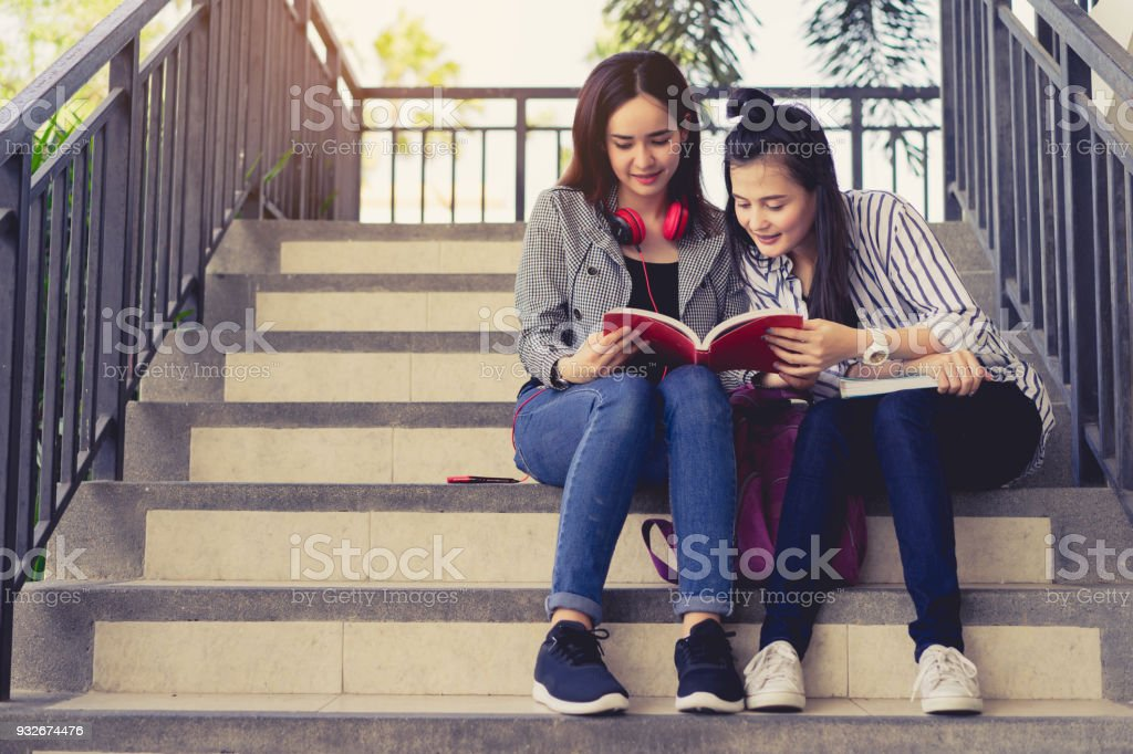Young women students together study reading book in university and knowledge at campus relaxing smile in summer season stock photo