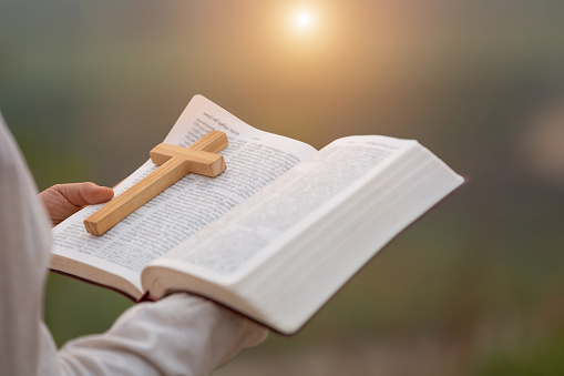 Young women study the scriptures. The sunrise background or whether the sunset The educational concept of Christian Tipitaka that is open and praying to God