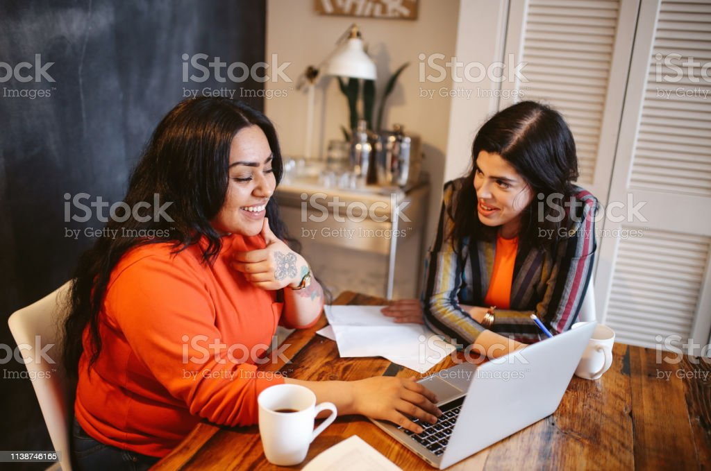 Young women studying or working late together in a downtown Los Angeles co-working space stock photo